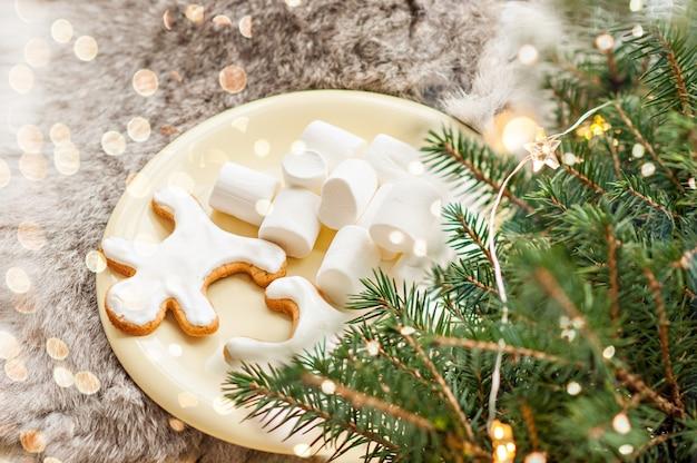 Auf einem gelben teller stehen lebkuchenmänner in weißer glasur und marshmallows