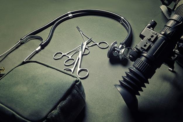 Auf einem grünen hintergrund liegen ein erste-hilfe-kasten, ein phonendoskop und eine schere sowie ein nachtsichtgerät. militärmedizinisches konzept