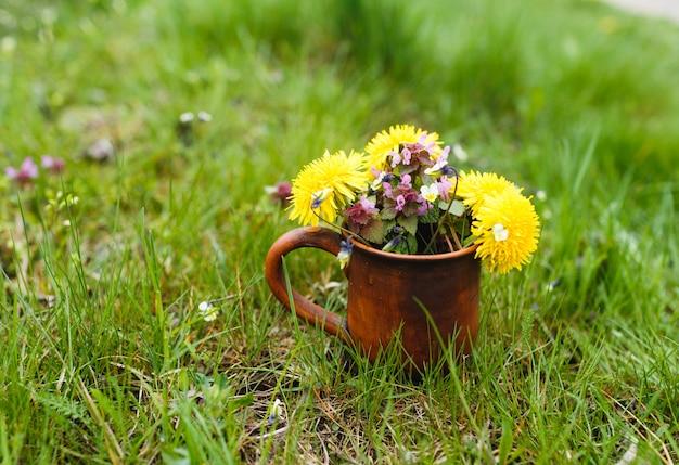Auf einem grünen rasen steht eine tonschale mit einem strauß heller frühlingsblumen. nahansicht