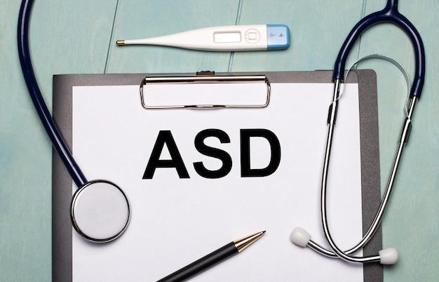 Auf einem hellblauen holzhintergrund befinden sich ein papier mit der aufschrift asd autism spectrum disorder, ein stethoskop, ein elektronisches thermometer und ein stift. medizinisches konzept