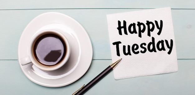 Auf einem hellblauen holztablett steht eine weiße tasse kaffee, ein griff und eine serviette mit der aufschrift happy dienstag.
