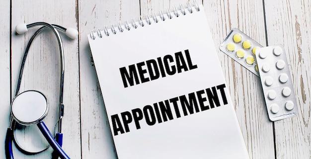 Auf einem hellen holztisch liegen ein stethoskop, pillen und ein notizbuch mit der aufschrift medical appointment. medizinisches konzept