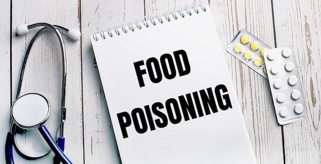 Auf einem hellen holztisch liegen ein stethoskop, tabletten und ein notizbuch mit der aufschrift food poisoning. medizinisches konzept