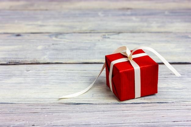 Auf einem hellen holztisch liegt ein kleines rotes geschenk, das mit einem weißen band zusammengebunden ist