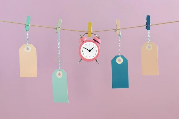 Auf einem hellen lila hintergrund hängen leere etiketten am seil. in der mitte steht ein kleiner rosa wecker