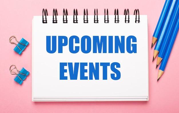 Auf einem hellrosa hintergrund, hellblauen bleistiften, büroklammern und einem weißen notizbuch mit dem text bevorstehende events