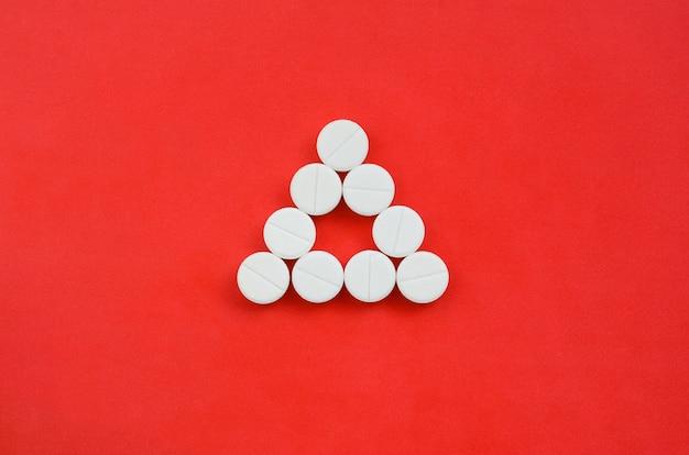 Auf einem hellroten hintergrund liegen mehrere weiße tabletten in form eines geraden dreiecks