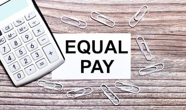 Auf einem hölzernen hintergrund ein weißer taschenrechner, weiße büroklammern und eine weiße karte mit dem text equal pay. sicht von oben.