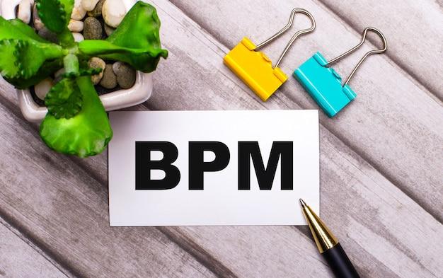 Auf einem hölzernen hintergrund eine weiße karte mit dem text bpm business process management, gelbe und grüne büroklammern und eine pflanze in einem topf. sicht von oben