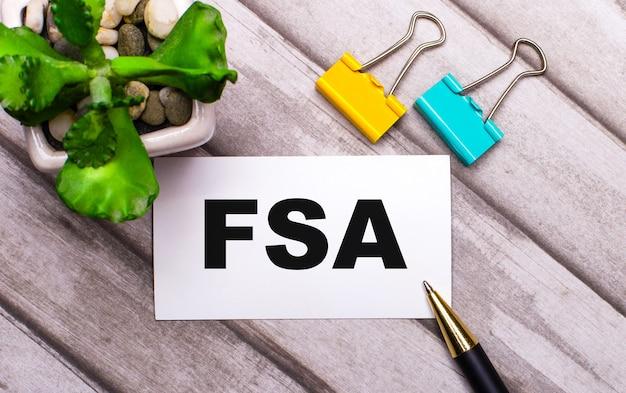 Auf einem hölzernen hintergrund eine weiße karte mit dem text fsa flexible spending account, gelbe und grüne büroklammern und eine pflanze in einem topf. sicht von oben