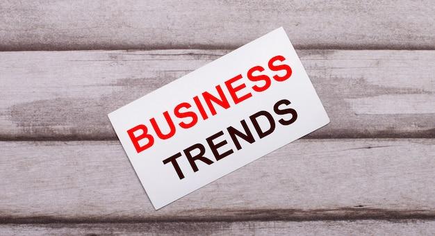 Auf einem hölzernen hintergrund gibt es eine weiße karte mit rotem text business trends