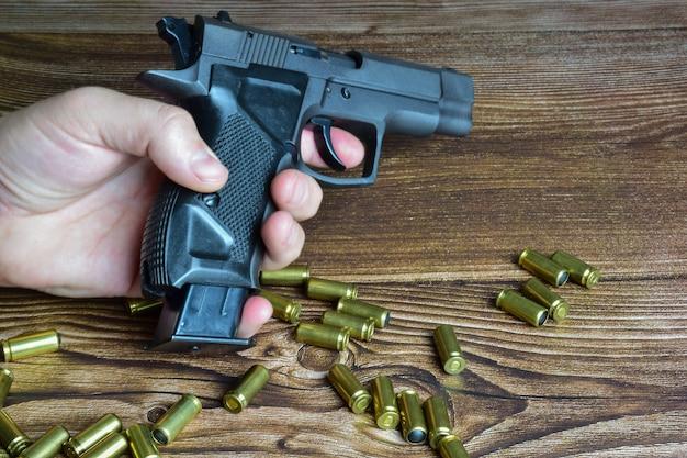 Auf einem hölzernen hintergrund gibt es viele verstreute patronen sowie eine hand, die eine traumatische pistole mit offenem clip hält
