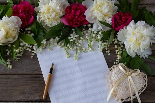 Auf einem hölzernen hintergrund pfingstrosen und maiglöckchen, papier für notizen