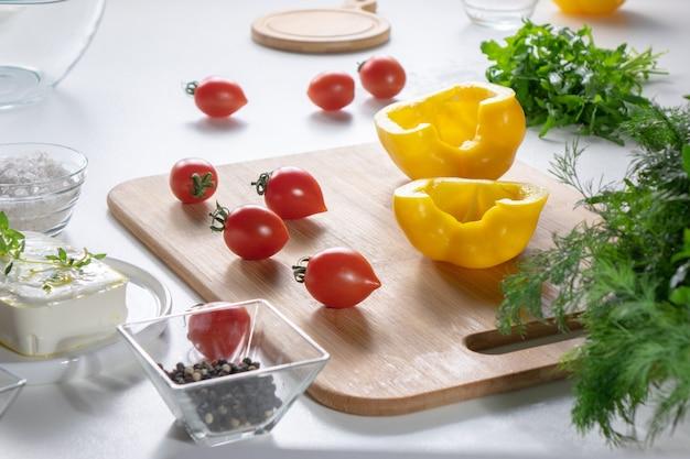 Auf einem holzbrett tomaten, hälften aus gelbem pfeffer, in einem teller käse und frischen kräutern auf einem weißen küchentisch. frische zutaten für salat. schritt für schritt kochen