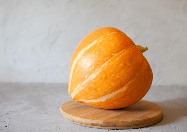 Auf einem holzständer liegt ein runder roher orangenkürbis