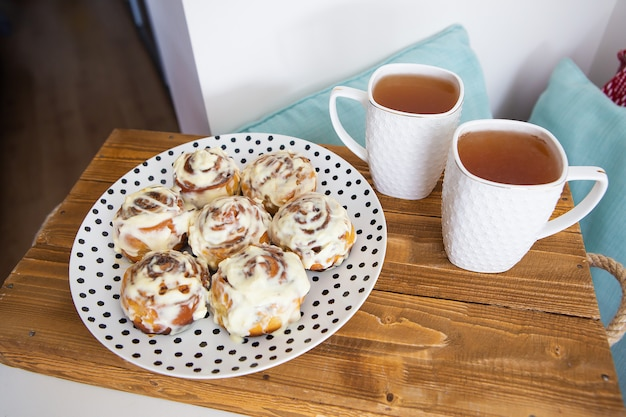 Auf einem holztablett stehen zwei tassen schwarzer tee, frische und duftende zimtschnecken in nahaufnahme auf einem teller mit tupfen.
