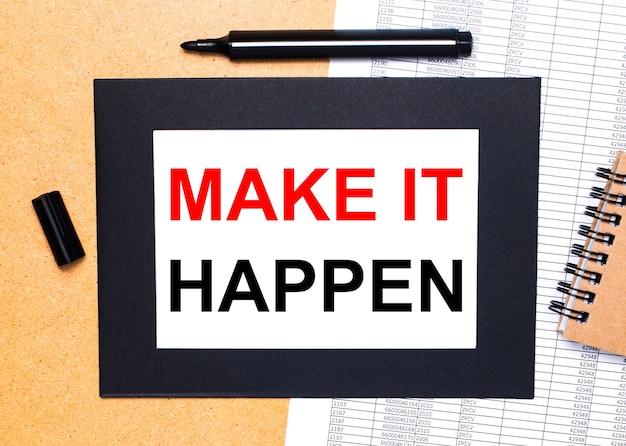Auf einem holztisch befinden sich eine schwarze offene markierung, ein brauner notizblock und ein blatt papier in einem schwarzen rahmen mit dem text make it happen