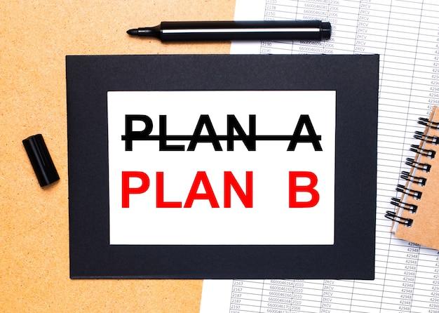 Auf einem holztisch befinden sich eine schwarze offene markierung, ein brauner notizblock und ein blatt papier in einem schwarzen rahmen mit dem text plan b. ansicht von oben