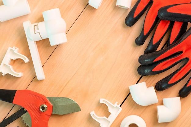 Auf einem holztisch befindet sich zubehör zur reparatur von wasserleitungen.