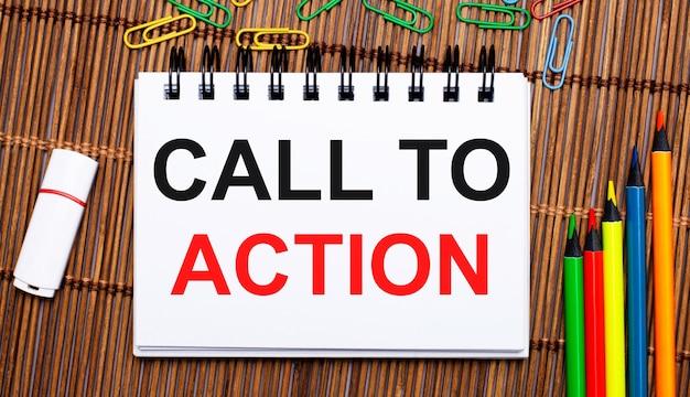 Auf einem holztisch bunte bleistifte, büroklammern, ein weißer usb-stick und ein notizbuch mit dem text call to action. flach legen