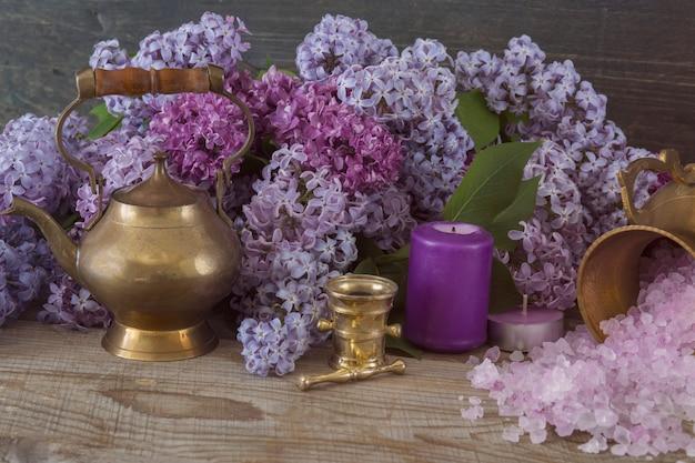 Auf einem holztisch ein bouquet von lila flieder, kerzen, salz, eine alte teekanne aus bronze - spa-artikel