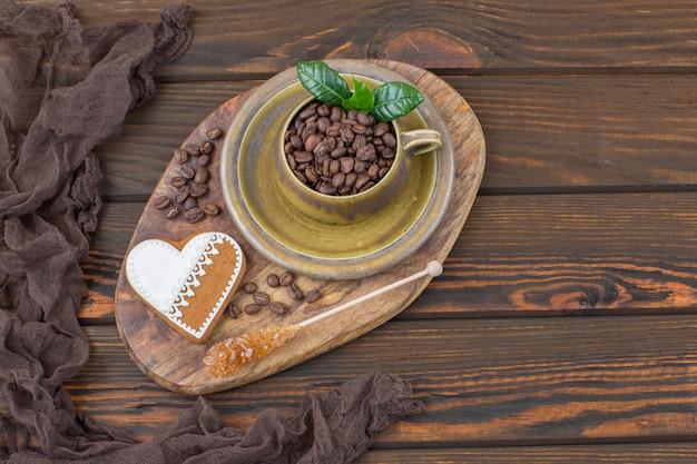 Auf einem holztisch eine tasse mit kaffeebohnen, einem herzförmigen lebkuchen und zucker