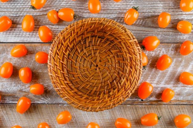 Auf einem holztisch lagen verstreute tomaten mit leerem korb flach