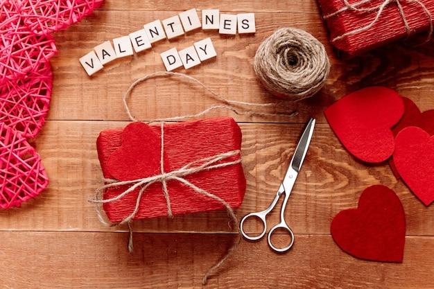 Auf einem holztisch liegt ein in wellpapier eingewickeltes handgemachtes geschenk. valentinstag