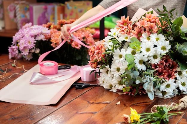 Auf einem holztisch liegt ein strauß mehrfarbiger chrysanthemen. der prozess der herstellung eines blumenstraußes durch einen floristen.