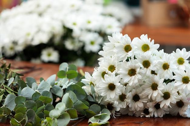 Auf einem holztisch liegt ein strauß weißer chrysanthemen. Premium Fotos