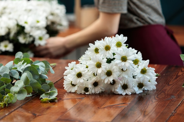 Auf einem holztisch liegt ein strauß weißer chrysanthemen.