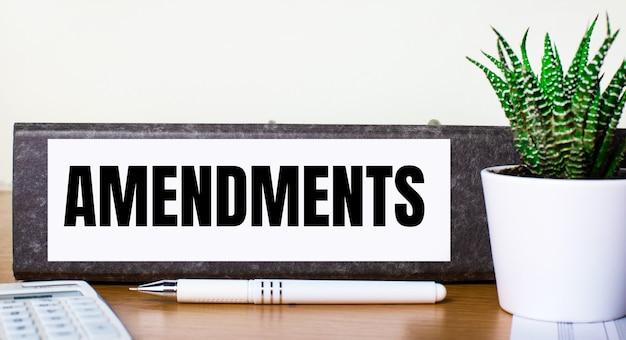Auf einem holztisch liegt eine aktenmappe mit einem amendments-teig, eine grüne pflanze im topf, ein stift und ein taschenrechner. unternehmenskonzept.