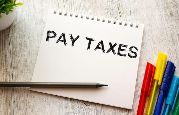Auf einem holztisch mit farbigen stiften liegt ein notizbuch auf einer feder mit dem text pay taxes auf einem weißen blatt. unternehmenskonzept.