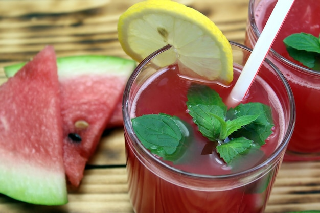 Auf einem holztisch stehen zwei gläser wassermelonensaft mit einem strohhalm, der mit minzblättern und zitrone dekoriert ist. köstlicher und gesunder saft.