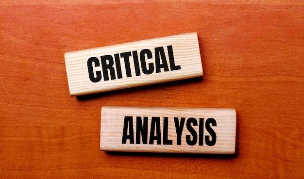 Auf einem holztisch stehen zwei holzklötze mit der textfrage kritische analyse.