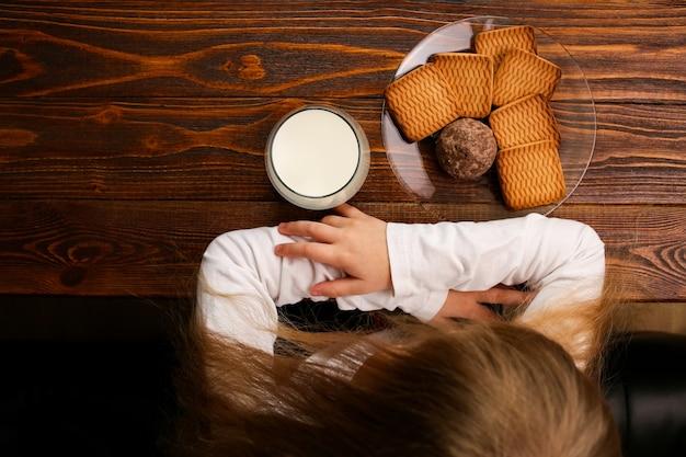 Auf einem holztisch steht ein glas milch und ein teller mit keksen für ein gesundes tägliches frühstück.