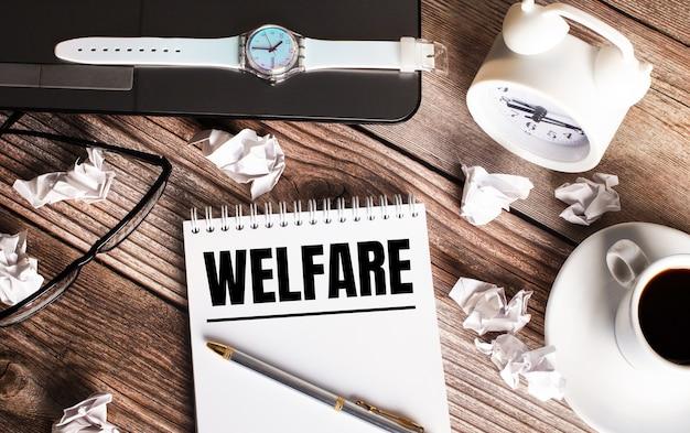 Auf einem holztisch steht eine tasse kaffee, eine uhr, gläser und ein notizbuch mit dem wort welfare. geschäftskonzept