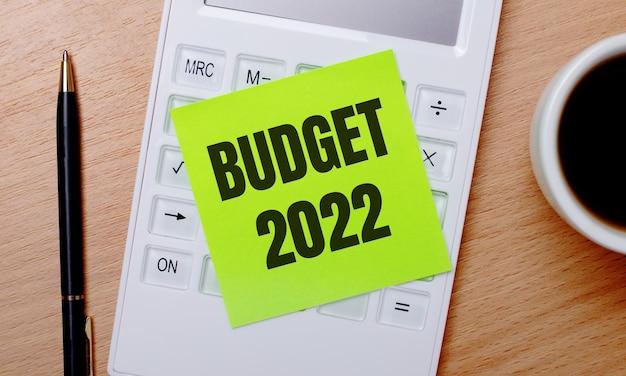 Auf einem holztisch steht kaffee in einer weißen tasse, ein stift und ein weißer taschenrechner mit einem grünen aufkleber mit dem text budget 2022. geschäftskonzept