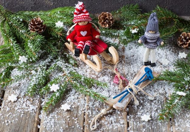 Auf einem holztisch, zweige aus tanne, schnee und ein mädchen auf einem schlitten und ein junge mit ski (spielzeug)