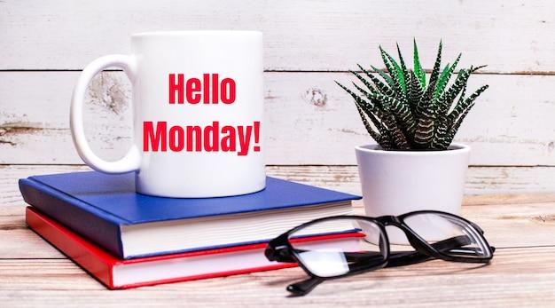 Auf einem leuchttisch stehen notizblöcke, eine topfpflanze, schwarz gerahmte gläser und eine weiße tasse mit der aufschrift hello monday.