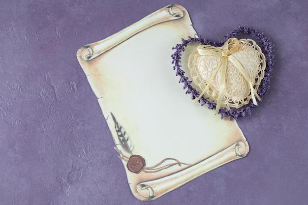 Auf einem lila hintergrund ein blatt papier und ein herz aus spitze - eine einladung, ein gruß