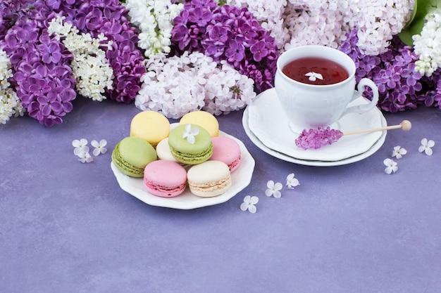Auf einem lila hintergrund eine tasse tee, makronen und ein strauß flieder