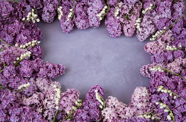 Auf einem lila hintergrund werden flieder und maiglöckchen mit einem rahmen gezeichnet