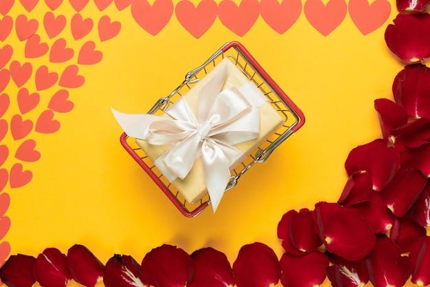 Auf einem orangefarbenen hintergrund für die inschrift liegt ein korb mit einem überraschungsgeschenk, roten rosenblättern und papierherzen