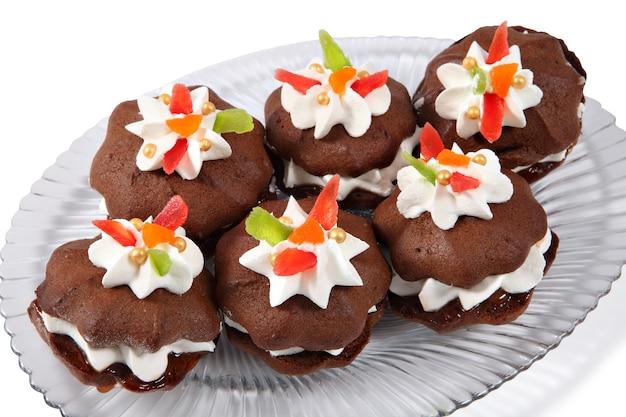 Auf einem ovalen teller liegen mehrere braune kuchenbrötchen mit sahnefüllung und dekoration aus sahne und kandierten früchten.