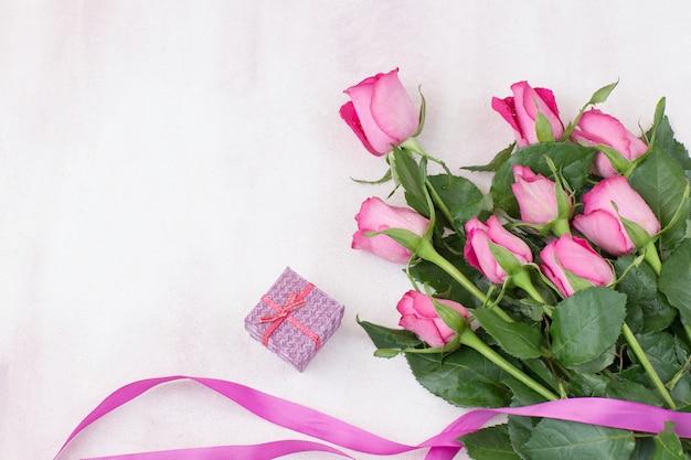 Auf einem rosa hintergrund ein strauß rosa rosen, eine schachtel mit einem geschenk und einem rosa band