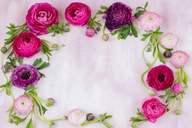 Auf einem rosa hintergrund werden durch einen ranunkel gestaltet