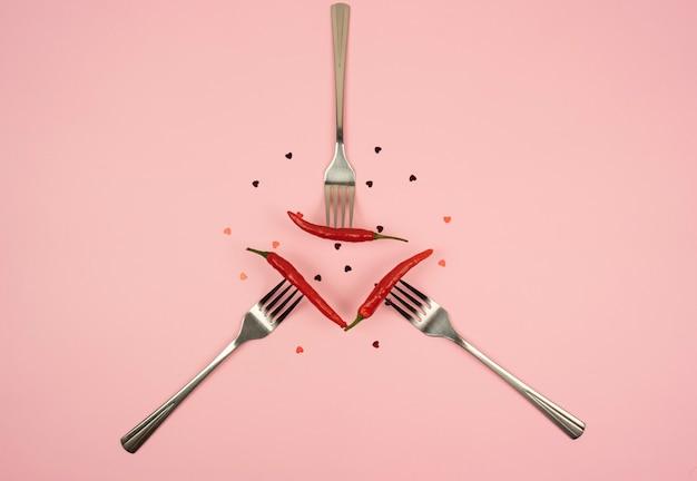 Auf einem rosa tisch liegen gabeln mit paprika und konfetti in form des herzens