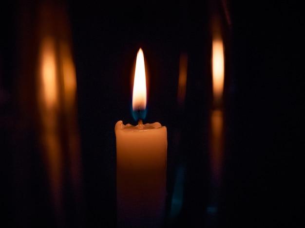 Auf einem schwarzen hintergrund brennen leuchtend gelbe kerzen, ein feiertag oder eine kirche