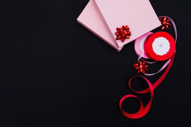 Auf einem schwarzen hintergrund gibt es rosa geschenkboxen. daneben befinden sich rosa satinbänder und geschenkschleifen. geschenkpapier. das konzept des 8. märz und des valentinstags.